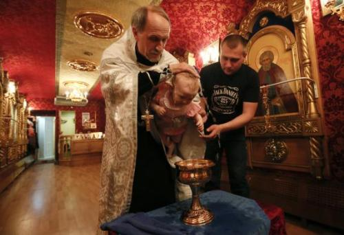 An Orthodox priest baptizes a baby at a church inside the Doctor Voino-Yasenetsky Saint Luka train at a railway station of Divnogorsk