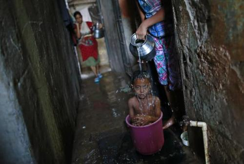 Manjunath takes a bath inside a bucket in a slum in Mumbai