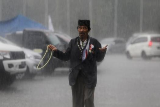 A man prays for good weather as he walks in the rain before presidential candidate Widodo arrives at a campaign rally in Bandung