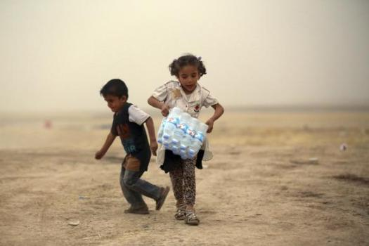 A girl, who fled from the violence in Mosul, carries a case of water at a camp on the outskirts of Arbil