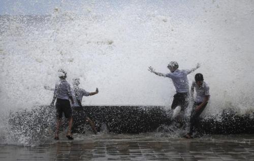 School boys get drenched in a large wave during high tide at a sea front in Mumbai