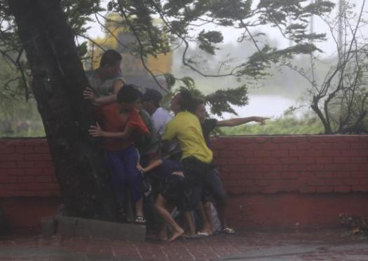 People take cover under tree after strong winds brought by Typhoon Rammasun, locally called Glenda, battered capital, metro Manila