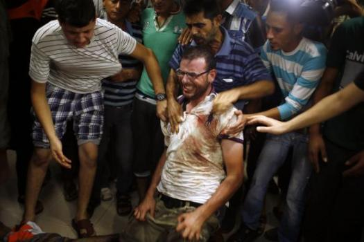 Palestinian man reacts next to the body of his relative, whom medics said was killed by Israeli shelling near a market in Shejaia, at a hospital in Gaza City