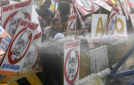 Protesters react as they are hosed by a water cannon  in Quezon city