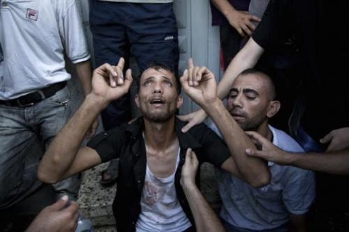 A Palestinian father reacts at the Shifa hospital morgue after his son was killed in an explosion that medics said killed eight children and two adults, and wounded 40 others at a public garden in Gaza City