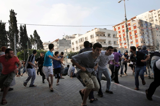 Palestinians take cover as warning Israeli air strikes are fired at a nearby building in Gaza City