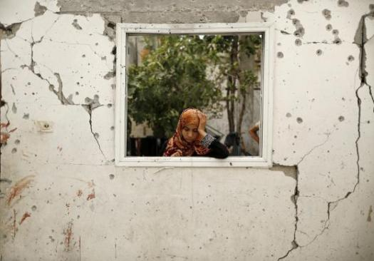 A relative reacts at a badly damaged house as bloodstains are seen on a damaged wall in Jabaliya refugee camp in the northern Gaza Strip