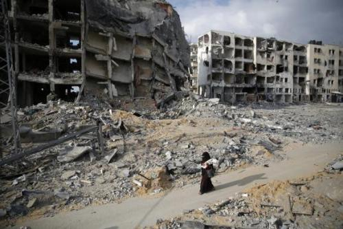 A Palestinian woman walks past destroyed buildings in Beit Lahiya in the northern Gaza Strip