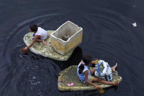 Children paddle, as they use discarded styrofoam as makeshift boats, to collect floating plastic recyclables on the Manila Bay to sell to junk shops, in Navotas City