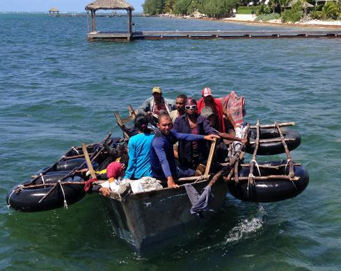 A home-made aluminium boat carrying 16 Cuban migrants pulls up to a dock in Grand Cayman island