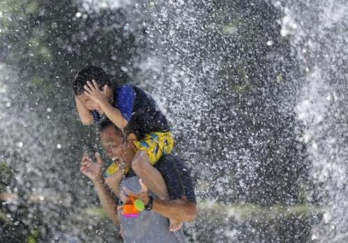 A boy sits on his father's shoulders as they cool down in the hot weather at a fountain in Tokyo