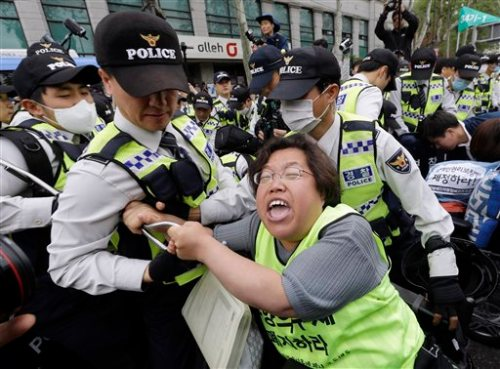 A member of the Korean Confederation of Trade Unions scuffles with police officers as they block her march during a May Day rally  in Seoul, South Korea, Sunday, May 1, 2016. Thousands of workers rallied to demand better working conditions and urge companies to stop using temporary employees. (AP Photo/Ahn Young-joon)