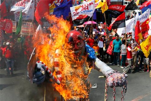 Protesters, mostly workers, burn an effigy of Philippine President Benigno Aquino III to mark the International Labor Day Sunday, May 1, 2016 in Manila, Philippines. The protesters are demanding among others, better wages and salaries, an end to contractual labor, better working conditions and retirement benefits, less taxes, public and not privatized social services, and the assertion of national sovereignty against foreign domination and control.(AP Photo/Bullit Marquez)