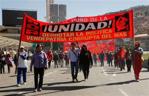 """Workers march in front of a banner with a message that reads in Spanish """"The fist of unity, defeating the traitorous policies of MAS,"""" during a May Day march, in La Paz, Bolivia, Sunday, May 1, 2015.  Left-wing groups, governments and trade unions were staging rallies around the world Friday to mark International Workers Day, also known as May Day. The banner refers to the government party Movement Towards Socialism, led by President Evo Morales. (AP Photo/Juan Karita)"""