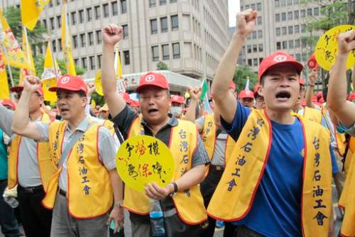 """Taiwanese workers shout slogans """"Strive for Working Right, Want Indemnifier"""" during a May Day rally in Taipei, Taiwan, Sunday, May 1, 2016. Thousands of protesters from different labor groups protest on the street to ask for raising minimum wage and shorter working hours. (AP Photo/Chiang Ying-ying)"""